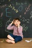 En pojke på bakgrunden av en svart tavla löser en svår uppgift Sitter med färgpennor och skrapar hans huvud arkivfoton