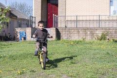 en pojke rider hans cykel på en varm sommardag Pojke som rider en cykel i gården på en bakgrund av ett tegelstenhus Royaltyfri Fotografi