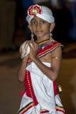 En pojke rymmer ett deltagande för kaurisnäckaskalstund i Esalaen Perahera i Kandy i Sri Lanka Arkivbild
