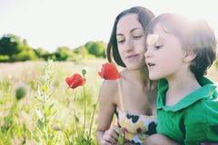 En pojke ser en blomma royaltyfri foto