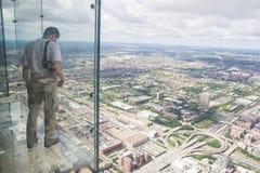 En pojke ser ut från den genomskinliga balkongen av thwillistornet Arkivfoton