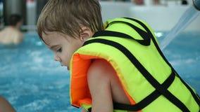 En pojke simmar i pölen Avkoppling och gyckel i pölen arkivbild