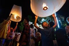 En pojke släpper en sväva lykta i Chiang Mai, Thailand Royaltyfria Bilder