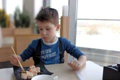 En pojke som äter med pinnar Royaltyfria Bilder