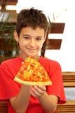 En pojke som äter pizza royaltyfria bilder