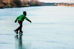 En pojke som åker skridskor på den djupfrysta sjön Royaltyfria Bilder