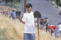 En pojke som bär ettskjorta för jorddag deltagande i ett träd som planterar vid rengöringen & de gröna volontärerna av Los Angele royaltyfria foton
