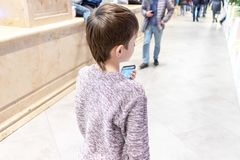 En pojke som går i gallerian och hänger en smartphone royaltyfri fotografi