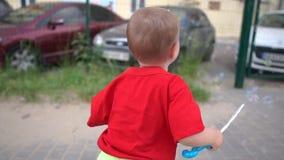 En pojke som gör såpbubblor på bakgrunden av suddiga bilar i ultrarapid arkivfilmer