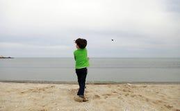 En pojke som kastar stenen in i havet Arkivbild