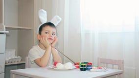 En pojke som kl?s som en hare, vet inte vilken f?rg som dekorerar f?rgen av p?sk?gget arkivfilmer