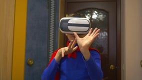 En pojke som kläs som en superhero i virtuell verklighetexponeringsglas, spelar hemma lager videofilmer