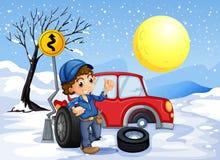 En pojke som reparerar en bil i ett snöig område Arkivfoto