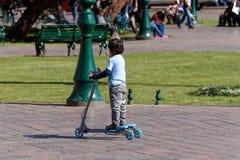 En pojke som rider hans sparkcykel royaltyfria foton