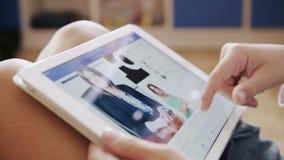 En pojke som ser den Facebook applikationen på Apple ipadskärm stock video