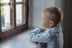 En pojke som ser i fönstret Arkivfoton
