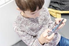 En pojke som sitter i gallerian och hänger en smartphone royaltyfria bilder