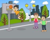 En pojke som spelar basket på parkeratecknade filmen Arkivfoton