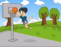 En pojke som spelar basket på parkeratecknade filmen Arkivbild