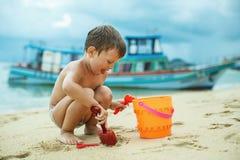 En pojke som spelar på stranden med sand Royaltyfria Bilder