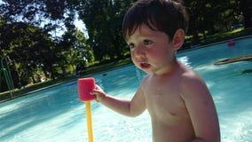 En pojke som spelar pölvatten Royaltyfria Foton