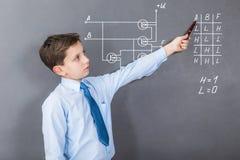 En pojke som studerar digitala chiper på CMOS-transistorer arkivbild