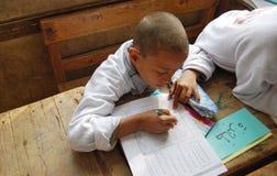 En pojke som studerar och skriver läxa i arabiska Royaltyfri Fotografi