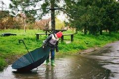 En pojke spelar i regnet Arkivfoton