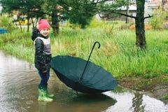 En pojke spelar i regnet Royaltyfria Bilder