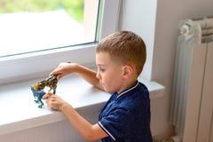 En pojke spelar med dinosauriediagram nära fönstret royaltyfria bilder