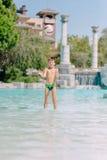 En pojke spelar med en boll i vattnet Royaltyfria Foton