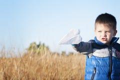 En pojke spelar med ett pappers- flygplan för leksak mot den blåa himlen i fältet Arkivbilder
