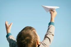 En pojke spelar med ett pappers- flygplan för leksak mot den blåa himlen i fältet Arkivbild