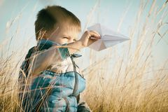 En pojke spelar med ett pappers- flygplan för leksak mot den blåa himlen i fältet Arkivfoton