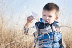 En pojke spelar med ett pappers- flygplan för leksak mot den blåa himlen i fältet Royaltyfri Bild