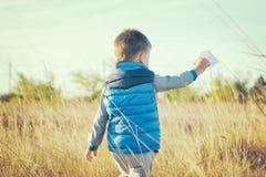 En pojke spelar med ett pappers- flygplan för leksak mot den blåa himlen i fältet Royaltyfria Foton