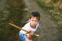 En pojke spelar med ett träsvärd Royaltyfria Foton