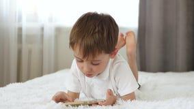En pojke spelar en mobil lek på en smartphone på en vit soffa arkivfilmer