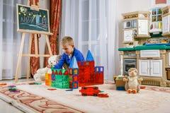 En pojke spelar vid en magnetisk konstruktör Intellektuella leksaker Arkivbilder