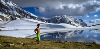 En pojke står bredvid bergsjön framme av snöberg i den soliga och molniga dagen arkivbild