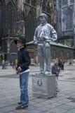 En pojke står framme av en statygataaktör som målas i silver i Wien i Österrike Arkivbilder