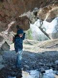 En pojke står under en bro Royaltyfri Fotografi