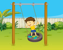 En pojke svänger på ett hjul Arkivbild