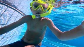 En pojke svävar i simbassängen som bär en dyka maskering lager videofilmer