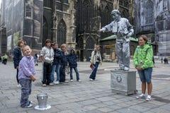 En pojke tappar ett mynt in i hinken av en statygataaktör som målas i silver i Wien i Österrike Royaltyfri Foto