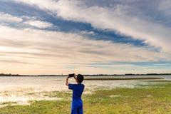 En pojke tar bilder av solnedgången royaltyfria foton