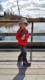 En pojke tycker om att fiska Fotografering för Bildbyråer