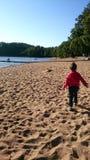 En pojke tycker om att spela vid sjön Arkivfoton