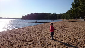En pojke tycker om att spela vid sjön Royaltyfri Bild