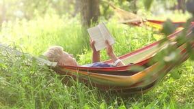 En pojke vaggar att ligga i hängmattan och läser en bok stock video
